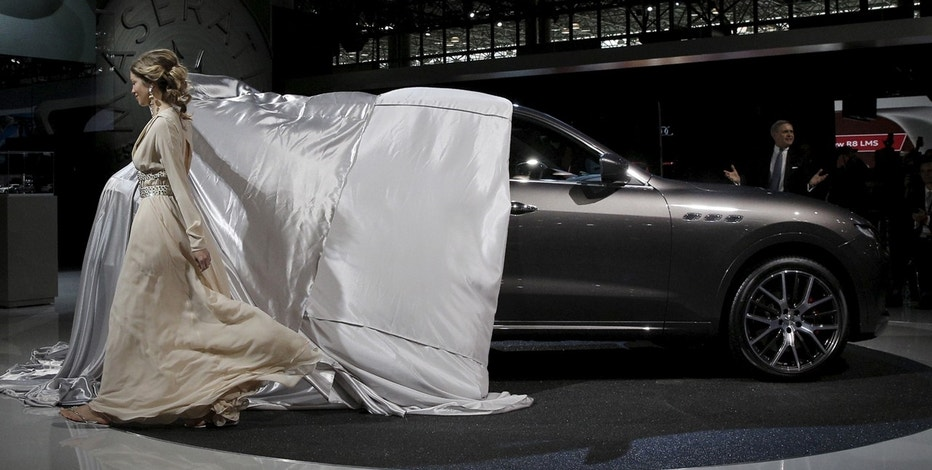 A model pulls the sheet to reveal the Maserati Levante SUV during the 2016 New York International Auto Show media preview in Manhattan, New York, March 23, 2016.