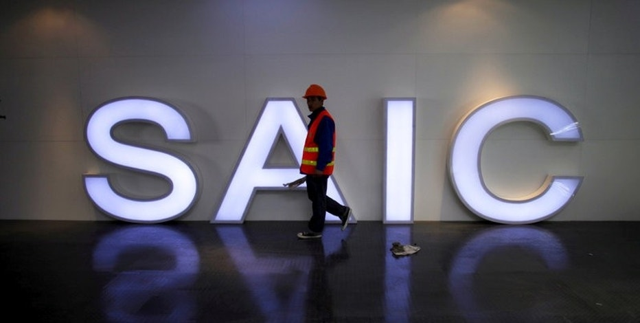 FILE PHOTO: A worker walks past a lighted signage of the Shanghai Automotive Industry Corporation (SAIC) before the opening of the 15th Shanghai International Automobile Industry Exhibition in Shanghai in this April 19, 2013 file photo.  REUTERS/Carlos Barria/File Photo