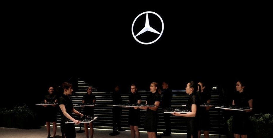Women hold translation equipment during a Daimler's event ahead of the Shanghai Autoshow in Shanghai, China April 18, 2017. REUTERS/Aly Song