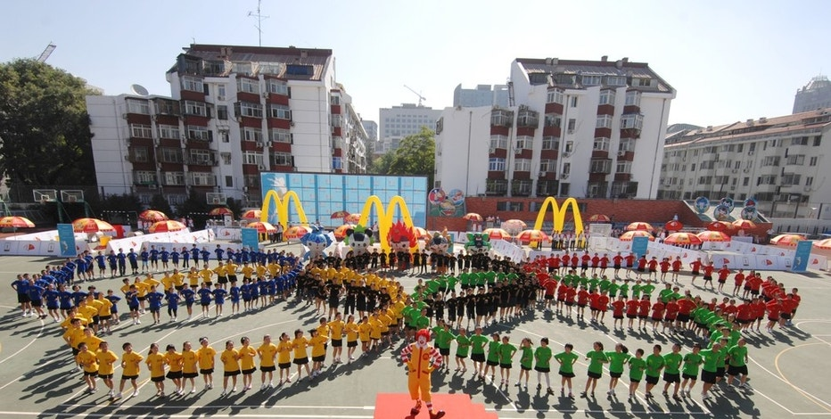 "In this photo released by McDonald's, one year before the Beijing 2008 Olympic Games, hundreds of children from Shi Jia Hu Tong primary school in Beijing, China show their Olympic spirit by forming the Olympic rings to mark the announcement of McDonald's 2008 Olympic Games sponsorship platform and its newest program ""McDonald's Champion Kids,"" Thursday, August 9, 2007.  The program, led by Global Ambassador and six-time U.S. Olympic gold medalist Michael Phelps, will enable up to 300 kids from around the world to travel to the 2008 Games, meet athletes, visit cultural sights and interact with kids from across the globe.   (AP Photo/McDonald's, Henny Ray Abrams, HO)"