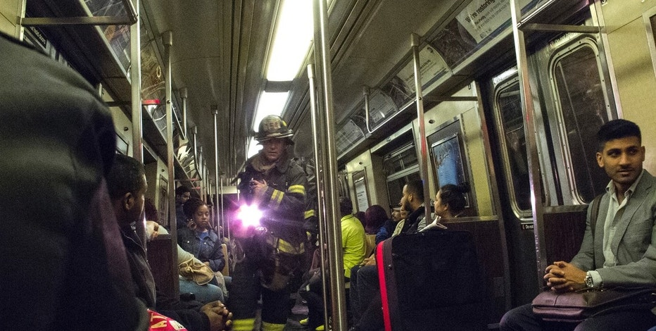 "A firefighter uses a flashlight as he makes his way past passengers through the derailed ""F"" train in the Woodside neighborhood located in the Queens borough of New York May 2, 2014. A New York City subway train carrying 1,000 riders derailed on Friday morning while traveling through a tunnel in the borough of Queens, injuring 19 people, city fire officials said. Fifteen people escaped with minor injuries while four more were transported to a hospital with potentially serious injuries, officials said. The incident, at 10:24 AM local time, involved a Manhattan-bound eight-car ""F"" line subway, they said. The cause of the derailment was not immediately known.  REUTERS/Connie Wang  (UNITED STATES - Tags: DISASTER SOCIETY TRANSPORT) - RTR3NKVA"
