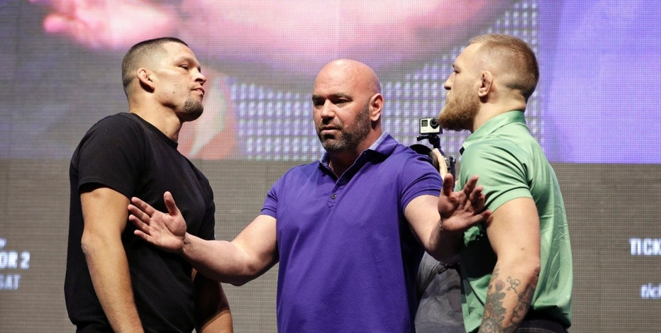 Dana White, center, stands between Nate Diaz, left, and Conor McGregor during a UFC 202 mixed martial arts news conference, Thursday, July 7, 2016, in Las Vegas. Diaz and McGregor are scheduled to fight at UFC 202 in Las Vegas. (AP Photo/John Locher)