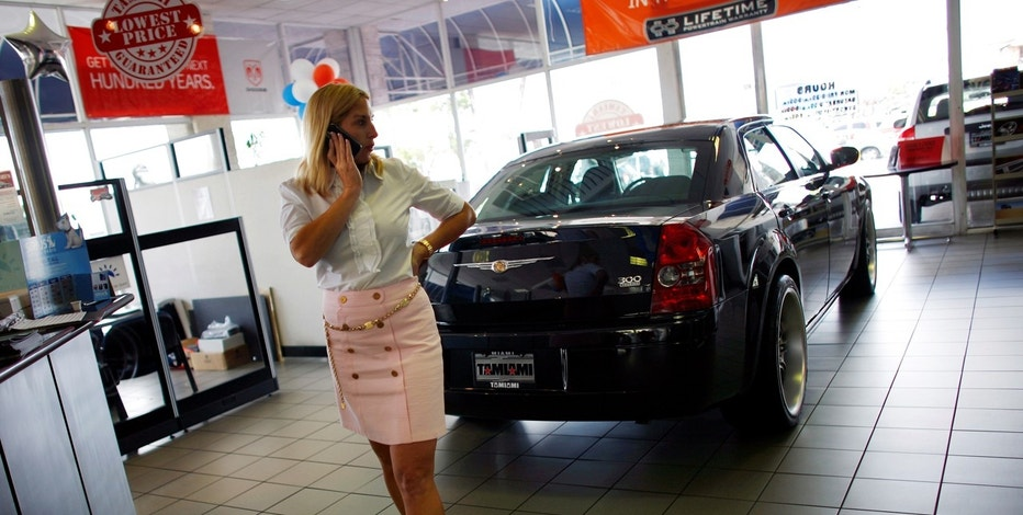 An employee of the Tamiami Chrysler Jeep Dodge dealership talks on the phone next to a Chrysler car in Miami, Florida May 14, 2009.