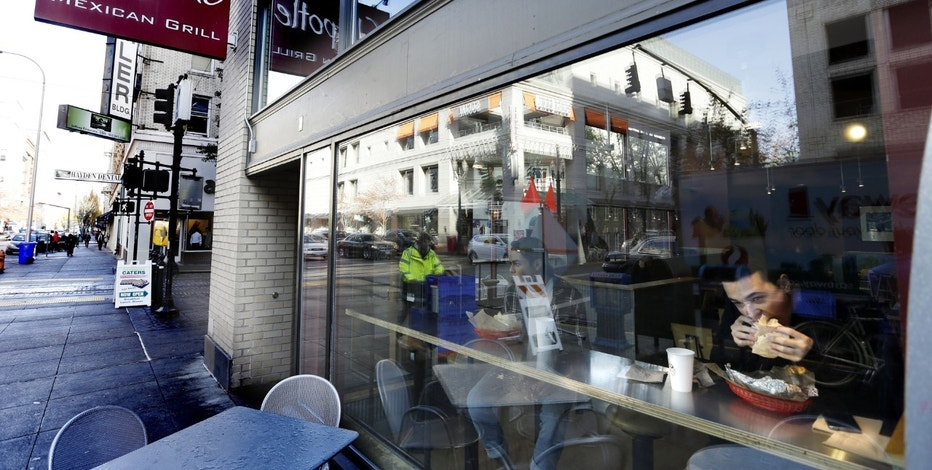 FILE - In this Wednesday, Nov. 11, 2015, file photo, a customer eats lunch at a Chipotle restaurant in Portland, Ore. Chipotle Mexican Grill, Inc. reports financial results, Tuesday, July 25, 2017. (AP Photo/Don Ryan, File)