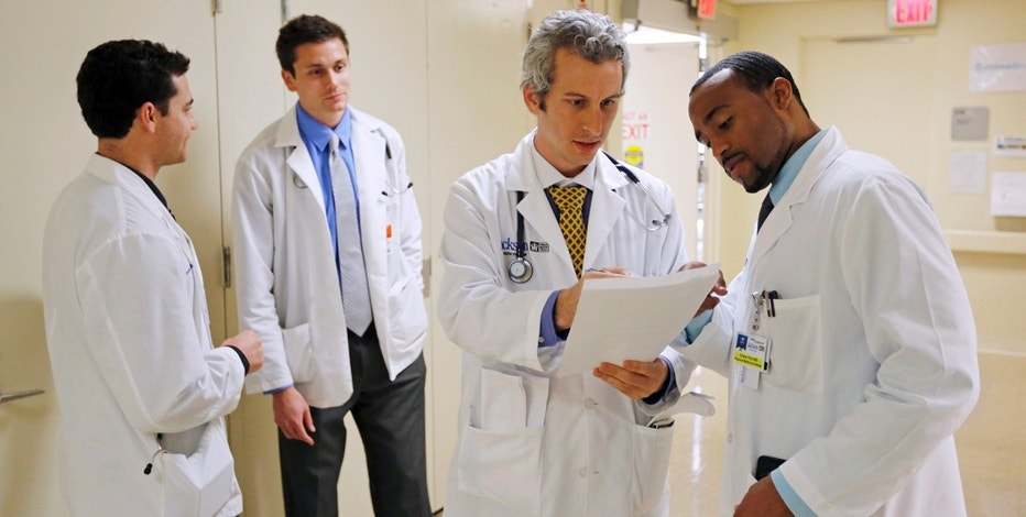 "Doctors Jordan Klein (2nd R) and Chane Price (R) confer as University of Miami interns Ignatios Papas (L) and Tim Sterrenberg (2nd L) look on in the Rehabilitation Unit of Jackson Memorial Hospital in Miami, September 30, 2013. The Obama administration accelerated its push to persuade individual Americans to sign up for the most extensive overhaul of the U.S. healthcare system in 50 years, the Affordable Care Act (commonly referred to as ""Obamacare"") even as the program's foes in Congress fought to delay its launch with the threat of a federal government shutdown. The Jackson Health System is the largest in Florida and one of the largest in the U.S.  REUTERS/Joe Skipper (UNITED STATES - Tags: HEALTH) - RTR3FGCZ"