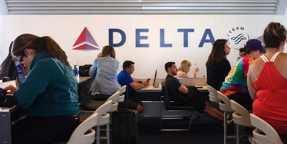 Passengers sit in stations equipped with iPads ahead of their flights at a Delta terminal in LaGuardia Airport in New York June 22, 2014. Picture taken June 22, 2014.   REUTERS/Adrees Latif  (UNITED STATES - Tags: TRANSPORT FOOD) - RTR3VPNM