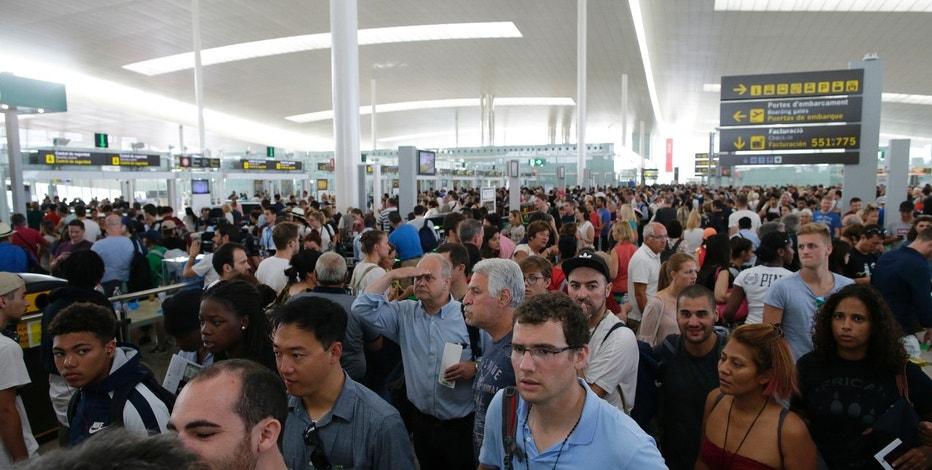Passengers wait to pass the security control at the Barcelona airport in Prat Llobregat, Spain, Friday, Aug. 4, 2017.  Security workers at Barcelona airport began partial strikes Friday which threatens more queuing chaos for passengers at one of Europe's most popular airports.  (AP Photo/Manu Fernandez)