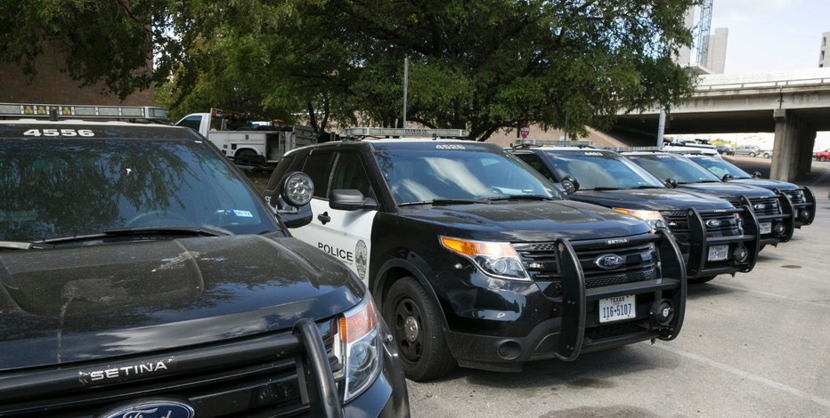 FILE - In this Tuesday, July 11, 2017, file photo, Austin police Ford utility vehicles are parked on East Eighth Street outside police headquarters in Austin, Texas.  (Jay Janner/Austin American-Statesman via AP, File)