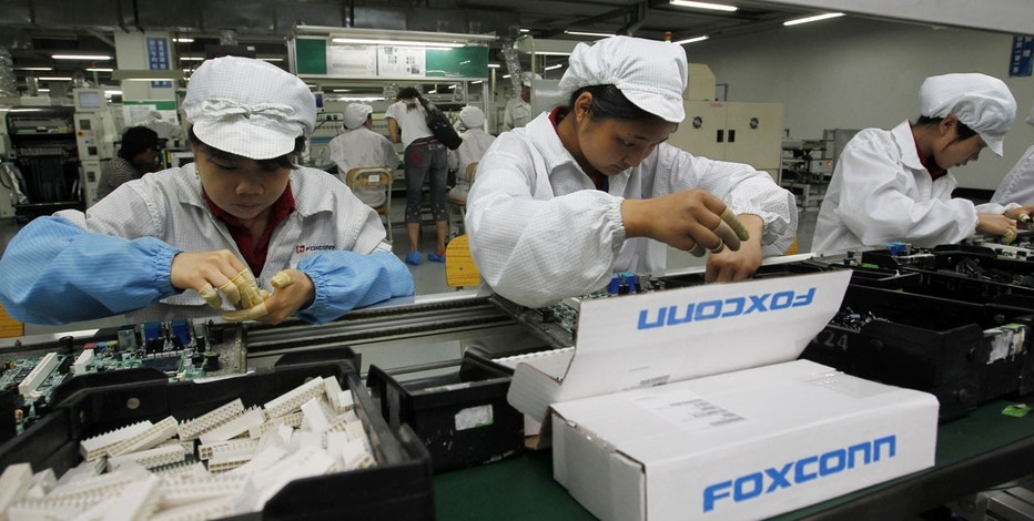 In this May 26, 2010 file photo, staff members work on the production line at the Foxconn complex in the southern Chinese city of Shenzhen, southern China.