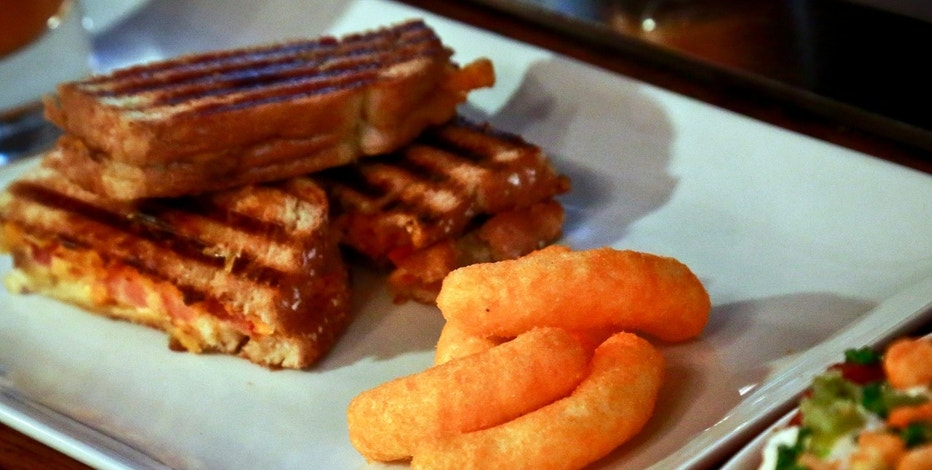 A grilled cheese made with Cheetos is shown during a press preview for a three-day pop-up restaurant featuring an all-Cheetos menu, Tuesday Aug. 15, 2017, in New York. (AP Photo/Bebeto Matthews)
