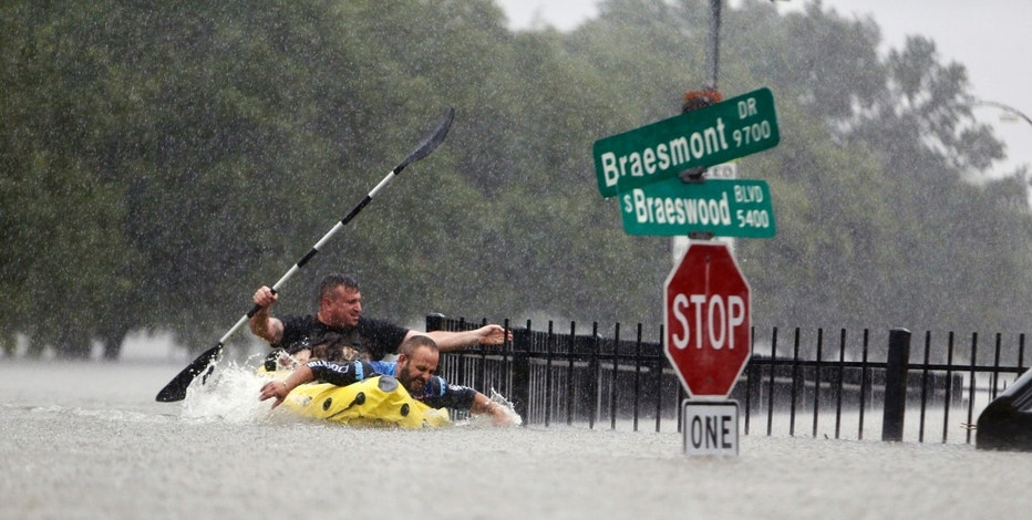 Two kayakers try to beat the current pushing them down an overflowing Brays Bayou from Tropical Storm Harvey in Houston, Texas, Sunday, Aug. 27, 2017. (Mark Mulligan/Houston Chronicle via AP)