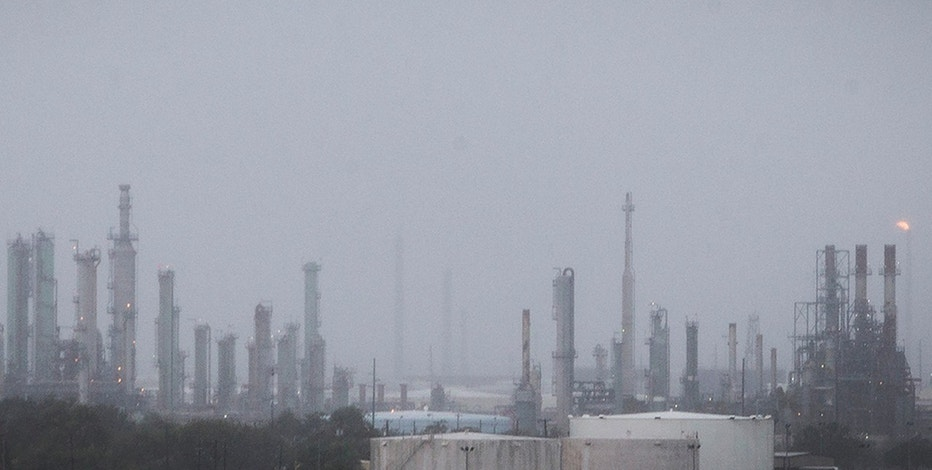 An oil refinery flare, right, continues to burn through wind and rain as Hurricane Harvey moves into Corpus Christi, Texas, on Friday, Aug. 25, 2017. Hurricane Harvey is expected to make landfall on the Texas coast Friday night or early Saturday morning. (Nick Wagner/Austin American-Statesman via AP)