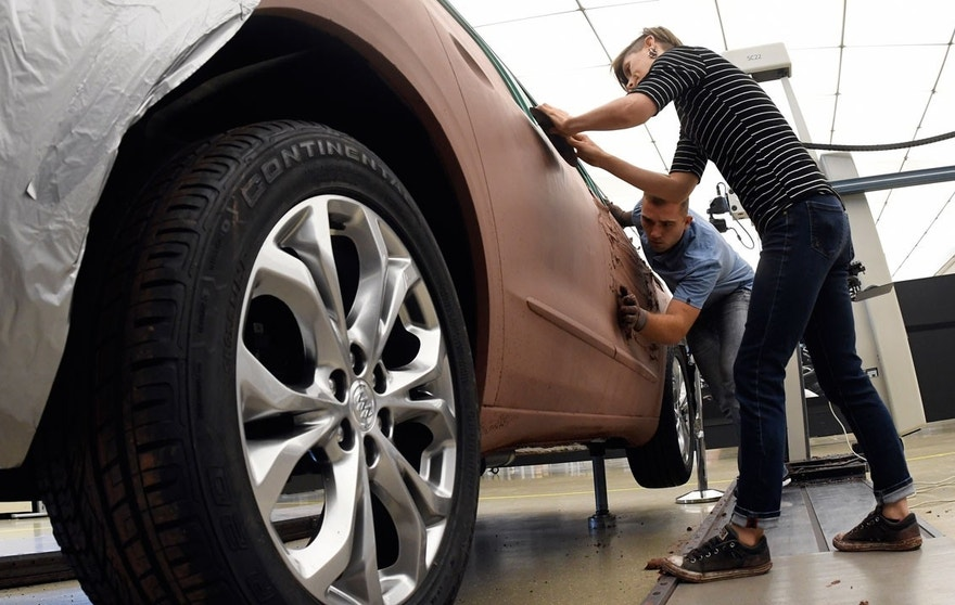 General Motors creative clay sculptors Gianna Ball, front, and Cameron Bogard pack clay onto a model of a 2018 Buick Enclave frame, Friday, Aug. 25, 2017 at the GM Tech Center in Warren, Mich.