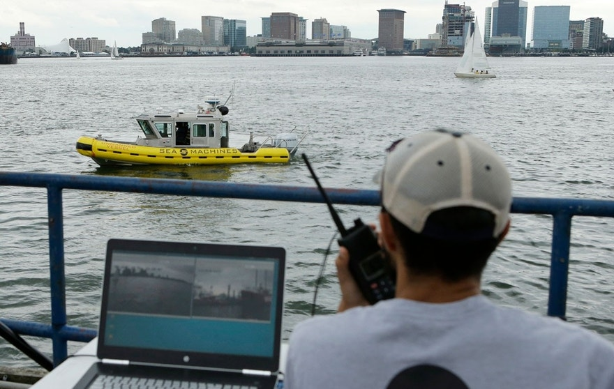In this Aug. 15, 2017 photo, computer scientist Mohamed Saad Ibn Seddik, of Sea Machines Robotics, uses a laptop to guide a boat outfitted with sensors and self-navigating software and capable of autonomous navigation in Boston Harbor. The boat still needs human oversight, but some of the world's biggest maritime firms have committed to designing ships that won't need any captains or crews - at least not on board.