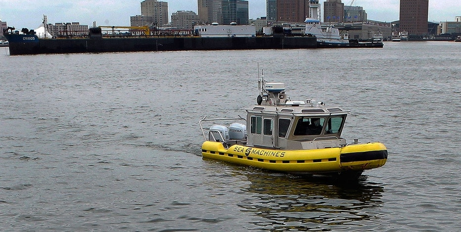 "In this Tuesday, Aug. 15, 2017 photo, a boat capable of autonomous navigation makes its way around Boston Harbor. The experimental workboat spent this summer dodging tall ships and tankers, outfitted with sensors and self-navigating software and emblazoned with the words ""UNMANNED VESSEL"" across its aluminum hull."