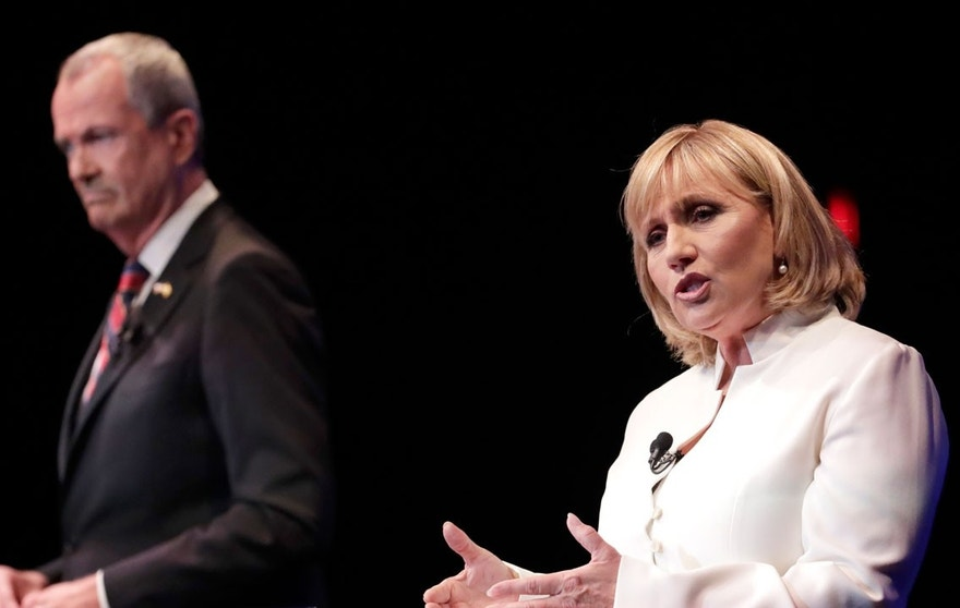 Democratic nominee Phil Murphy, left, listens as Republican nominee Lt. Gov. Kim Guadagno, right, answers a question during a gubernatorial debate at the New Jersey Performing Arts Center, Tuesday, Oct. 10, 2017, in Newark, N.J.