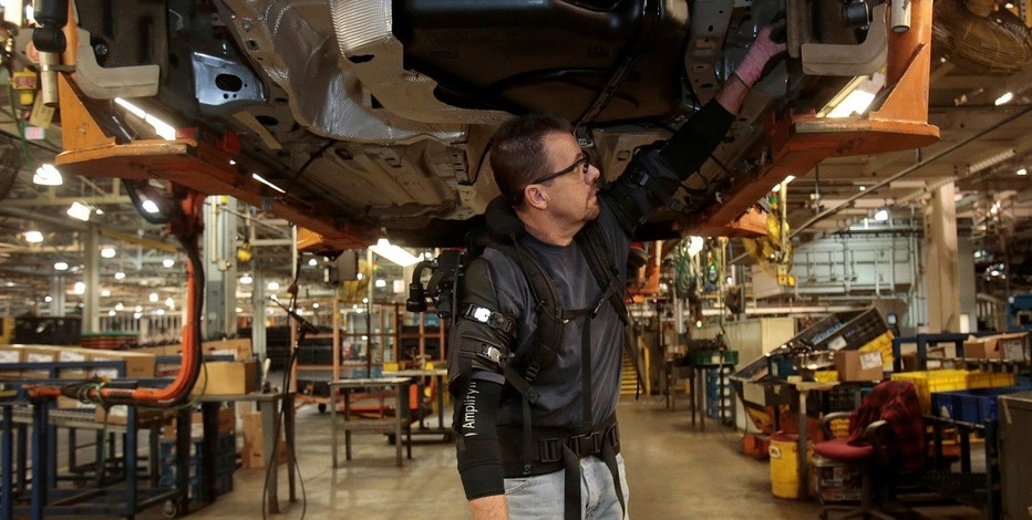 Ford Motor Co assembly worker Paul Collins wears a EksoVest as he works on the assembly line producing the Ford Focus and C-max at Wayne Assembly plant in Wayne, Michigan, U.S., November 9, 2017.