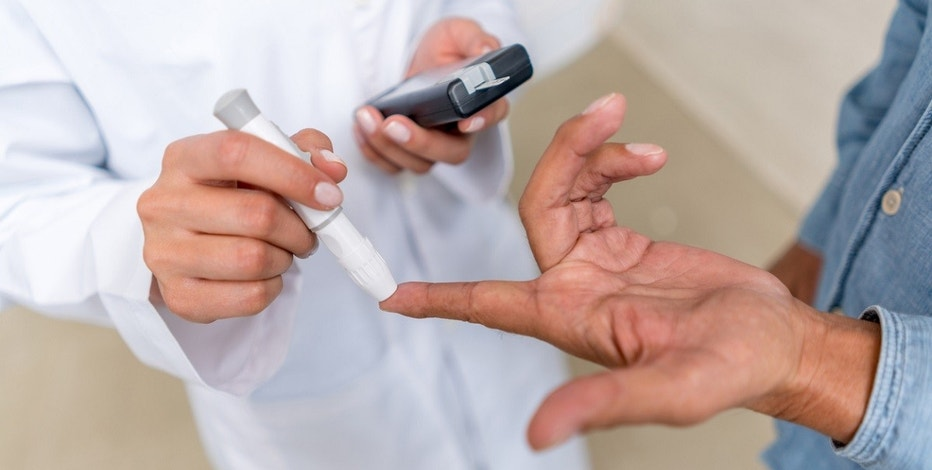 Man checking sugar level with glucometer using a blood sample