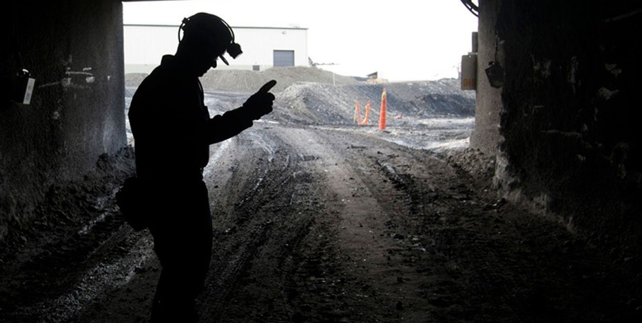 In this Nov. 9, 2010, file photo, a mine employee stands in the entry of the Signal Peak Energy's Bull Mountain mine in Roundup, Mont.