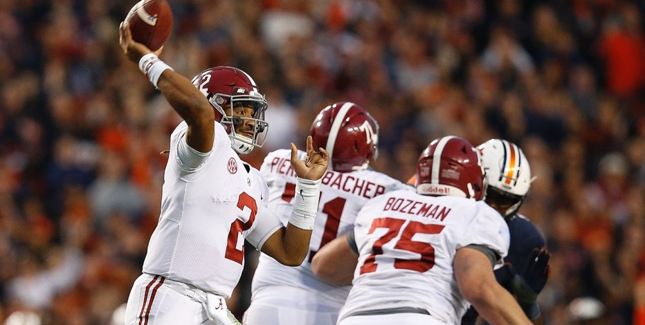 FILE - In this Nov. 25, 2017, file photo, Alabama quarterback Jalen Hurts throws the ball during the second half of the Iron Bowl NCAA college football game, in Auburn, Ala. The Associated Press voters prefer Alabama over Ohio State. In the final Top 25 of the regular season, the Crimson Tide was No. 4 and the Buckeyes were No. 5. (AP Photo/Brynn Anderson, File)