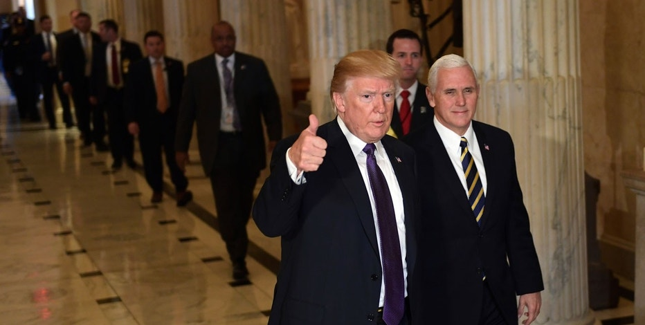 President Donald Trump gives a thumbs up as he walks with Vice President Mike Pence as he departs Capitol Hill in Washington, Thursday, Nov. 16, 2017.