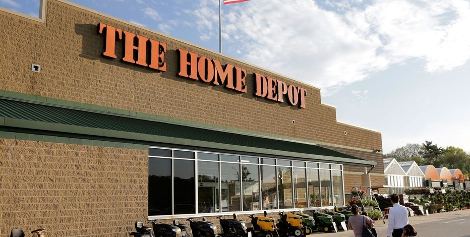 In this Wednesday, May 18, 2016, file photo, people approach an entrance to a Home Depot store in Bellingham, Mass.