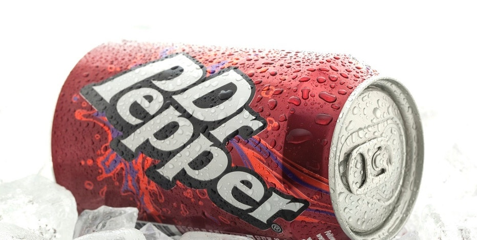 Swindon, United Kingdom - April 25, 2014: Can of Dr Pepper on a bed of ice overa white background, The drink was created in the 1880s by Charles Alderton of Waco, Texas and first served around 1885