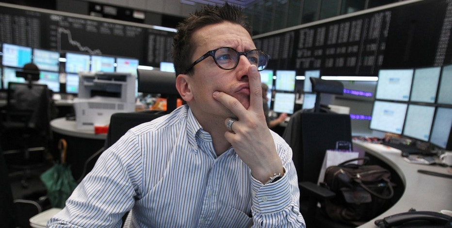 A trader reacts at his desk in front of the DAX board at the Frankfurt stock exchange November 9, 2011. REUTERS/Alex Domanski (GERMANY - Tags: BUSINESS)