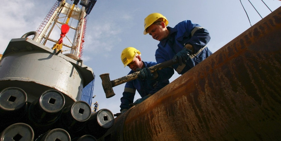 Workers prepare equipment on the drilling tower of the Shakhrinav-1P exploratory well at the Sarikamysh gas field in Shakhrinav district, some 50 km (31 miles) west of Dushanbe December 7, 2010. Russia's Gazprom zarubezhneftegaz will start drilling the first prospect well at the Sarikamish gas field on Tuesday.  REUTERS/Nozim Kalandarov (TAJIKISTAN - Tags: ENERGY POLITICS BUSINESS)