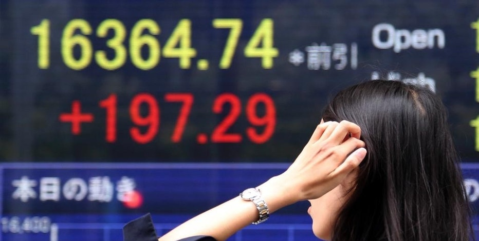 A woman walks by an electronic stock board of a securities firm in Tokyo, Thursday, Sept. 25, 2014. Asian stock markets were mostly higher Thursday after a surge in new home sales in the U.S. bolstered sentiment. But gains were limited by worries about Europe's stagnant economy and violence in Iraq and Syria. (AP Photo/Koji Sasahara)