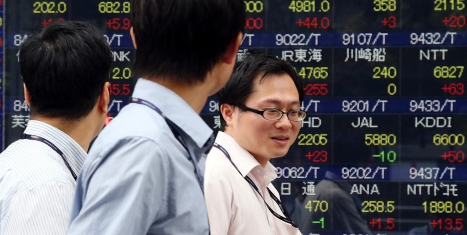 People walk by an electronic stock board of a securities firm in Tokyo, Thursday, Sept. 25, 2014. Asian stock markets were mostly higher Thursday after a surge in new home sales in the U.S. bolstered sentiment. But gains were limited by worries about Europe's stagnant economy and violence in Iraq and Syria. (AP Photo/Koji Sasahara)