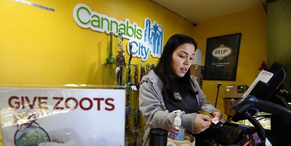 In this Tuesday, Dec. 30, 2014, photo, Cannabis City clerk Jessica Mann scans a customer's ID as she rings up a purchase of marijuana at the shop in Seattle. A year into the nation's experiment with legal, taxed marijuana sales, Washington and Colorado find themselves with a cautionary tale for Oregon, Alaska or other states that might follow suit: They're wrestling not with the federal interference many initially feared, but with competition from their own medical marijuana systems or even outright black market sales. (AP Photo/Elaine Thompson)