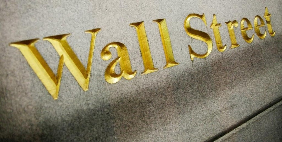FILE - This Oct. 8. 2014, file photo, shows a Wall Street address carved into the side of a building in New York. U.S. stocks are opening the year on a strong note, but energy stocks slipped as the price of crude oil resumed its slide, Friday, Jan. 2, 2015. (AP Photo/Mark Lennihan, File)