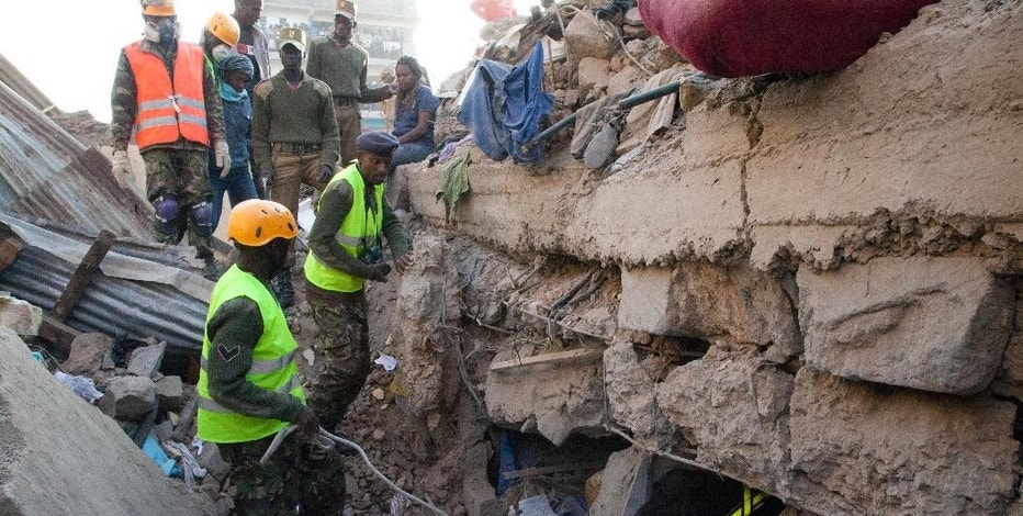 Rescue workers use a sniffer dog to look for survivors at the site of the collapsed building in the capital Nairobi, Kenya , Monday, Jan. 5, 2015. The residential building in the Huruma neighborhood of Nairobi collapsed on Sunday and according to the Kenya Red Cross, a dozen people have so far been rescued but an unknown number are still feared trapped. (AP Photo/Sayyid Azim)