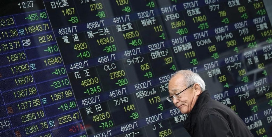 A man looks at an electronic stock board of a securities firm in Tokyo, Tuesday, Jan. 6, 2015. Asian stocks sank Tuesday for a second day as slumping oil prices and concern Greece might leave the European currency union fueled unease about the global growth outlook. Tokyo's Nikkei 225 tumbled 2.4 percent to 16,990.52. (AP Photo/Eugene Hoshiko)