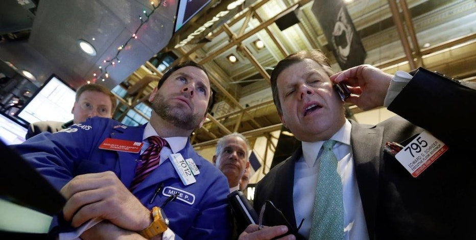 Specialist Michael Pistillo, left, trader Edward Schreier, right, on the floor of the New York Stock Exchange Tuesday, Jan. 6, 2015. The U.S. stock market is edging higher in early trading as the price of oil extends its slump. (AP Photo/Richard Drew)