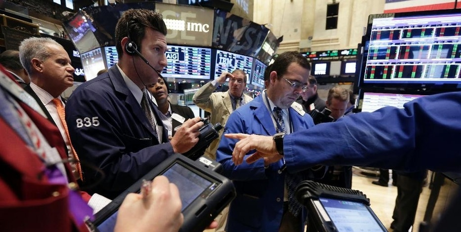 Traders gather at a post on the floor of the New York Stock Exchange Tuesday, Jan. 6, 2015. The U.S. stock market is edging higher in early trading as the price of oil extends its slump. (AP Photo/Richard Drew)