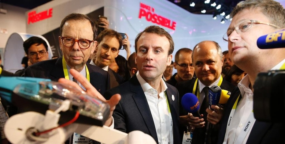 French finance minister Emmanuel Macron, center, tours the Parrot booth with Parrot CEO and founder Henri Seydoux, right, and Louis Schweitzer, left, Tuesday, Jan. 6, 2015, at the International CES in Las Vegas. (AP Photo/John Locher)