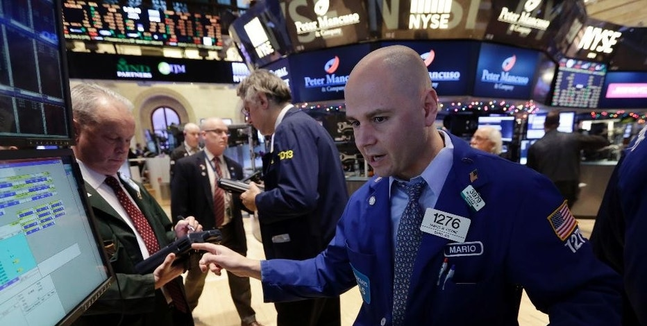 Specialist Mario Picone, right, works at his post on the floor of the New York Stock Exchange Tuesday, Jan. 6, 2015. The U.S. stock market is edging higher in early trading as the price of oil extends its slump. (AP Photo/Richard Drew)