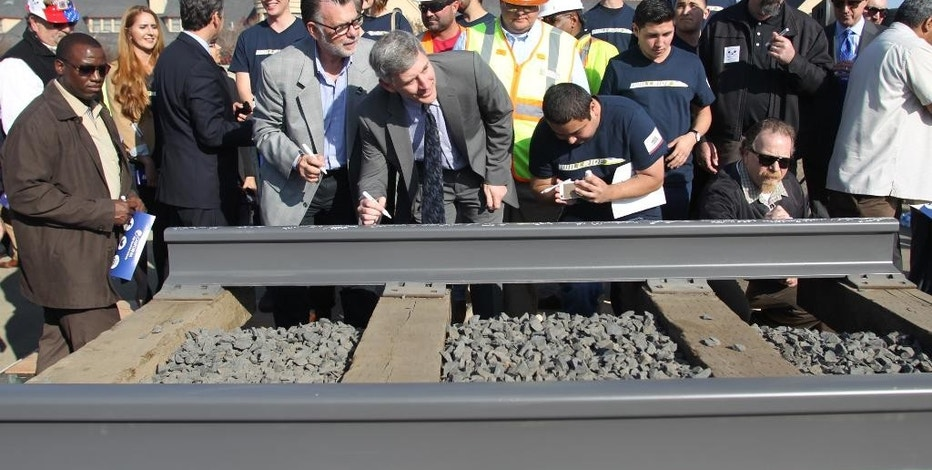 Dignitaries and VIP's line up to sign a portion of the rail at the California High Speed Rail Authority ground breaking event, Tuesday, Jan. 6, 2015 in Fresno, Calif.  The $68 billion project faces challenges from Republicans in Congress eager to reduce government spending and Central Valley farmers suing to block the train from crossing their fields. The train would whisk travelers at 200 mph between Los Angeles and San Francisco in less than three hours. (AP Photo/Gary Kazanjian)