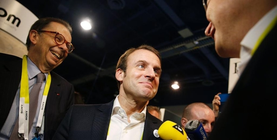 French finance minister Emmanuel Macron, center, tours the Parrot booth with Parrot CEO and founder Henri Seydoux, right, and Louis Schweitzer, Tuesday, Jan. 6, 2015, at the International CES in Las Vegas. (AP Photo/John Locher)