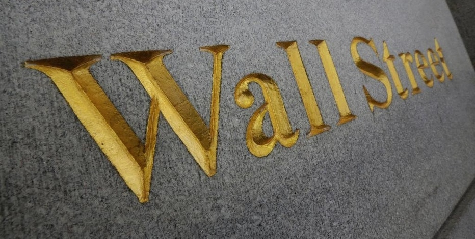 FILE - In this Oct. 2, 2014 file photo, Wall Street is etched in the facade of a building in New York's Financial District. U.S. stocks are rising in early trading Wednesday, Jan. 7, 2014, as the price of oil steadies. (AP Photo/Richard Drew, File)