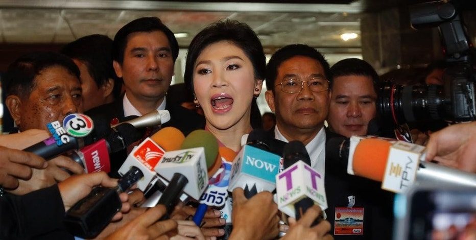 Thailand's former Prime Minister Yingluck Shinawatra, center, talks to reporters on her arrival at parliament in Bangkok, Thailand Friday, Jan. 9, 2015. Thailand's military-appointed legislature will start an impeachment hearing Friday against Yingluck, a move analysts say is aimed at ensuring the ousted leader stays out of politics for the foreseeable future. (AP Photo/Sakchai Lalit)