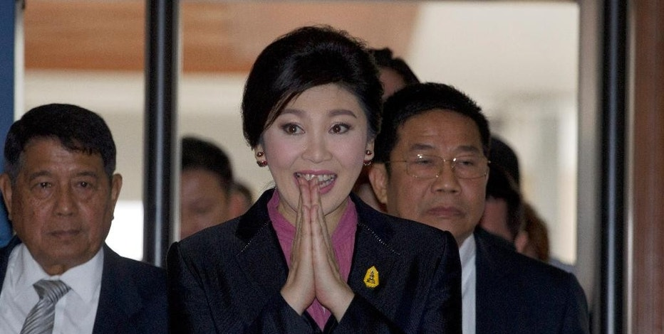 Thailand's former Prime Minister Yingluck Shinawatra, center, arrives at parliament in Bangkok, Thailand Friday, Jan. 9, 2015. Thailand's military-appointed legislature will start an impeachment hearing Friday against Yingluck, a move analysts say is aimed at ensuring the ousted leader stays out of politics for the foreseeable future. (AP Photo/Sakchai Lalit)