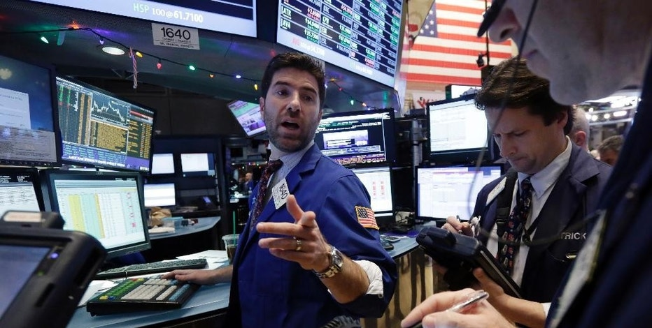 Specialist Thomas McArdle, center, works with traders at his post on the floor of the New York Stock Exchange, Thursday, Jan. 8, 2015. U.S. stocks rose in early trading on Thursday, boosted by a combination of positive economic news from the U.S. and expectations of stimulus from Europe's central bank. (AP Photo/Richard Drew)