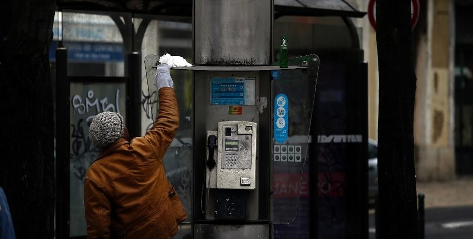 A man places a plastic bag on top of a Portuguese Portugal Telecom telephone box in Lisbon, Wednesday, Jan. 7, 2015. Portugal Telecom shares have fallen sharply on the Lisbon stock exchange, a day after authorities said they were investigating possible fraud at the company. (AP Photo/Francisco Seco)