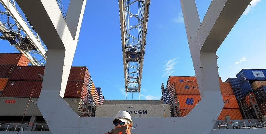 FILE - In this Monday, Jan. 2, 2014 file photo, a dock worker communicates on a walkie-talkie while a ship to shore crane loads containers onto a ship at the Georgia Ports Authority Garden City terminal, in Savannah, Ga. The Commerce Department releases wholesale trade inventories for November 2014 on Friday, Jan. 9, 2015.  (AP Photo/Stephen B. Morton, File)