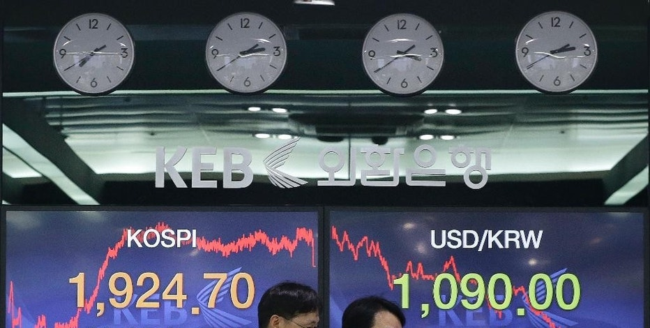 Currency traders pass by screens showing the Korea Composite Stock Price Index (KOSPI) and foreign exchange rate, right, at the foreign exchange dealing room of the Korea Exchange Bank headquarters in Seoul, South Korea, Friday, Jan. 9, 2015.  Asian stocks extended gains Friday after other global markets bounced back from a rocky start to the year and oil prices stabilized after dramatic plunges. The Korea Composite Stock Price Index rose 1.05 percent, or 20.05, to close at 1,924.70. (AP Photo/Ahn Young-joon)