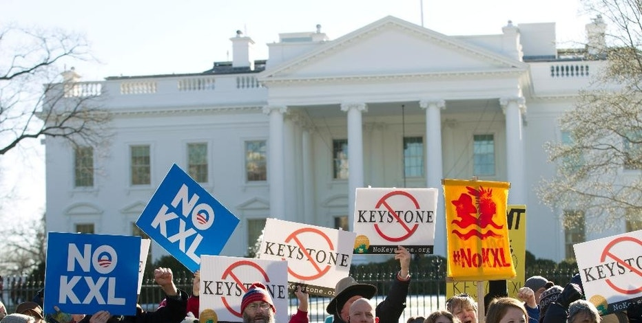 Dozens of demonstrators rally in support of Obama's pledge to veto any legislation approving the Keystone XL pipeline, outside the White House in Washington on Saturday, Jan. 10, 2015. (AP Photo/Jose Luis Magana)