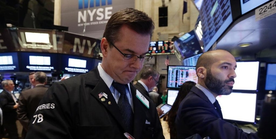 Trader Steven Caro, left, works on the floor of the New York Stock Exchange Monday, Jan. 12, 2015. Stocks are moving lower in early trading, led by a decline in energy stocks as the price of oil fall again. (AP Photo/Richard Drew)